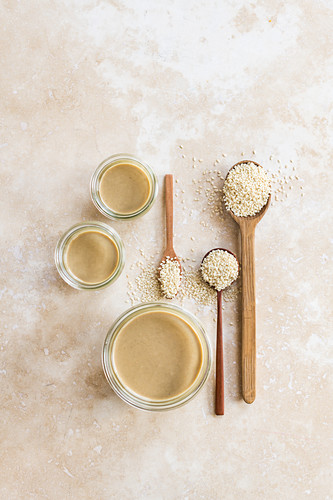 Tahini in jars next to sesame seeds on spoons (seen from above)
