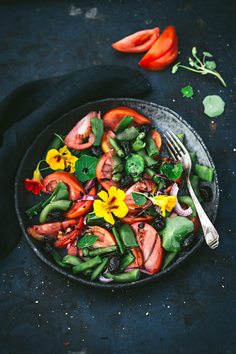 Tomato and bean salad with flowers in a grey bowl