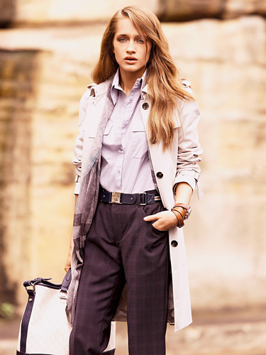 A young woman wearing purple trousers, a blouse and a trench coat with a bag