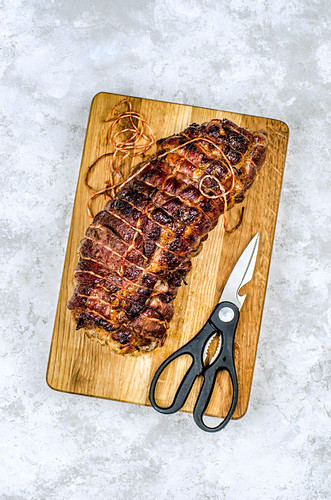 Meat loaf on a wooden Board with ? scissors to remove the rope