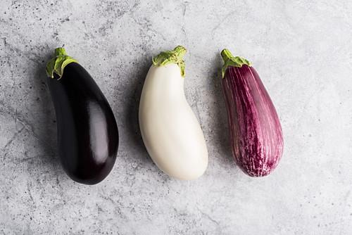 Three different coloured aubergines