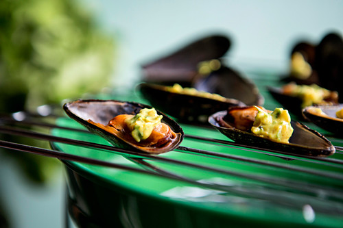 Grilled mussels with a curry dip on a grill
