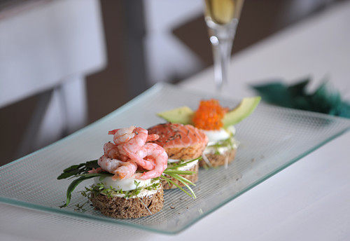 A trio of canapes with prawns, salmon and caviar on a serving platter
