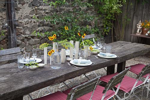 Flower arrangements on rustic set table on terrace