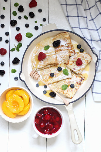 Pancakes with berries and honey served with peaches and red fruit jelly