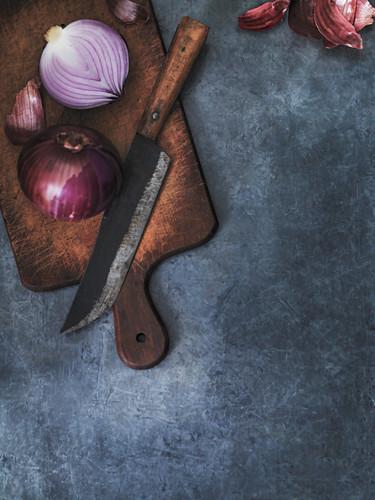 Rote Zwiebel mit Messer auf Schneidebrett