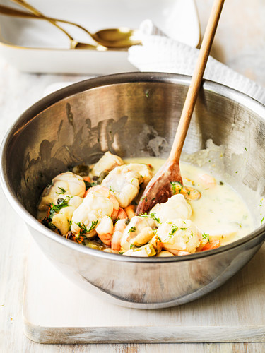Mixing the ingredients for seafood pie