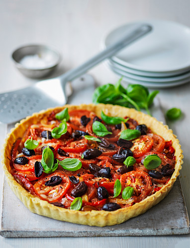 Olive and tomato tart served with basil