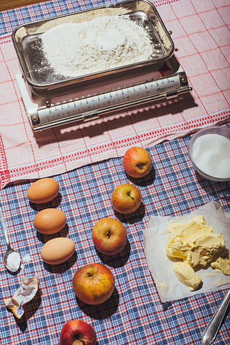 Ingredients for sunken apple pie on a checked tablecloth