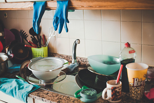 Messy table with dirty dishes in the sink on the kitchen
