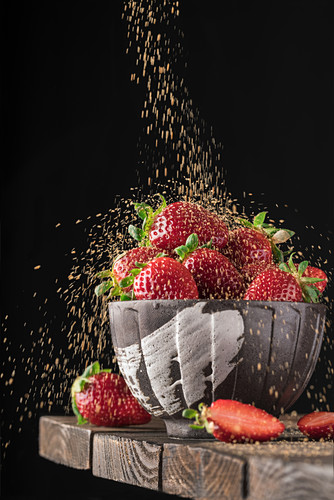 Full bowl of fresh red strawberry in rain of golden crumbs falling