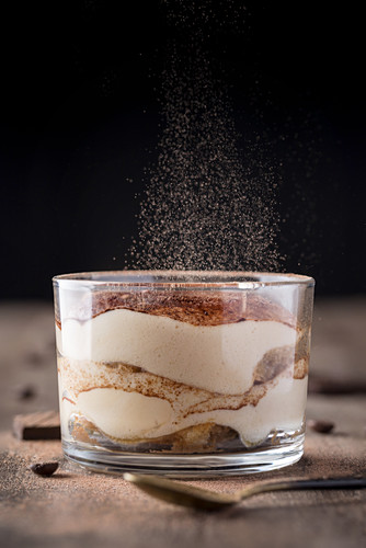 Fresh tiramisu dessert in glass with particles of cocoa dust falling on top