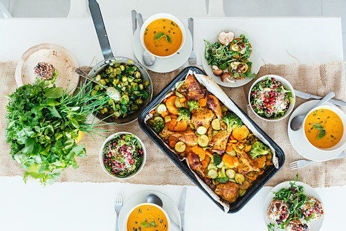 Lunch table filled with autumn dinner - pumpkin soup, roasted chicken and salad