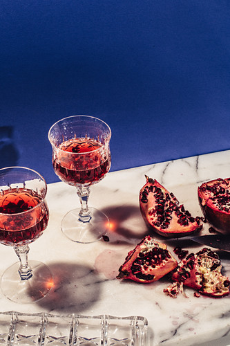 Pomegranate vodka drinks with sliced pomegranates on a marble plate