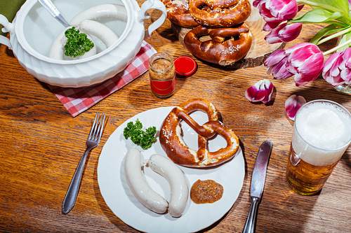 White sausages with sweet mustard and a pretzel on a plate, with pale beer