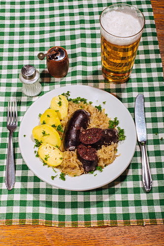 Black pudding with boiled potatoes and sauerkraut on a checked tablecloth, with pale beer
