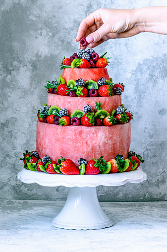 Red cake with watermelon, strawberries, raspberries, kiwi, blackberries and rosemary