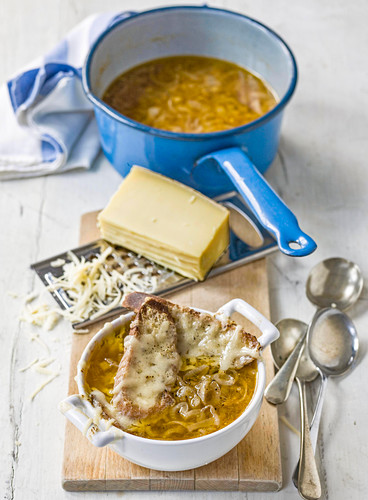 French onion soup in bowl and saucepan with baguette croutons and grated gruyere cheese