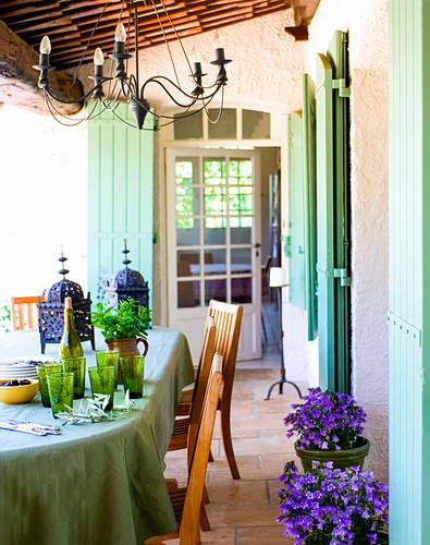 Marokkanisch gedeckter Tisch mit Minze, Oliven und Laternen auf Terrasse