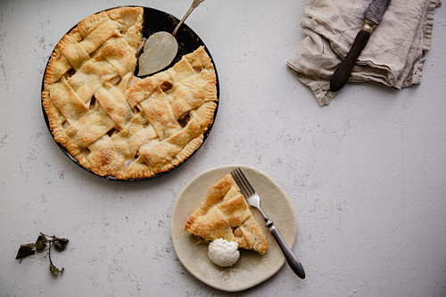 Apple pie with lattice decoration and a slice served on handmade ceramic plate with a scoop of vanilla ice-cream