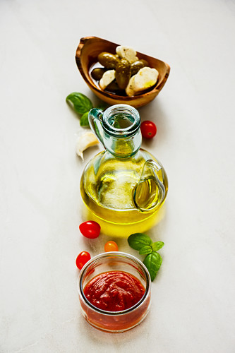 Italian cooking ingredients - Tomato sauce, olives, mozzarella, basil leaves and oil
