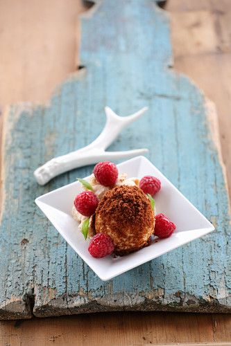 Quark dumplings with a nougat filling and rum and raisin ice cream with raspberries