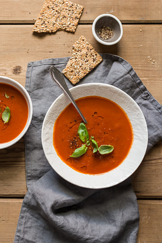 Tomato soup with fresh basil on a wooden table
