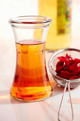 Homemade rose blossom vinegar in a mason jar with Aceto Balsamico Bianco