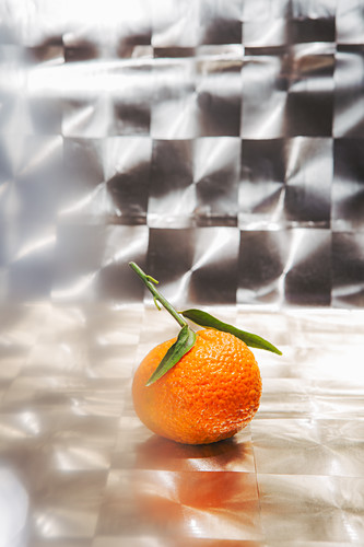 A mandarin with a leaf against a reflective background