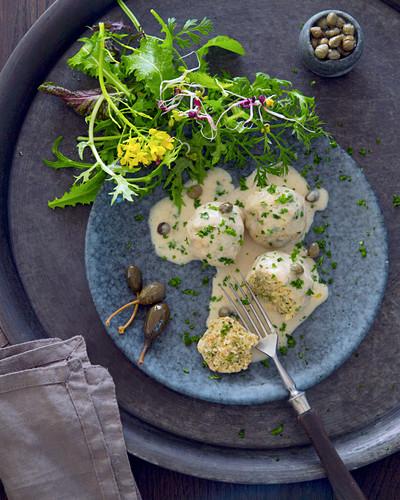 Vegetarian grain dumplings with caper sauce and garden salad