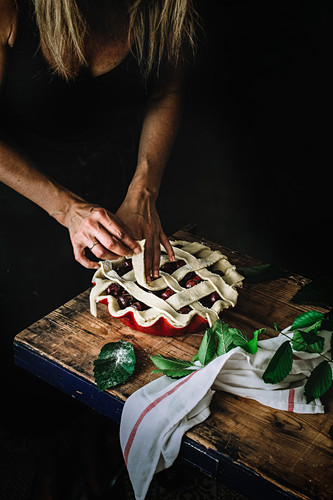 Crop shot of woman creating lattice top pie crust with straps of dough covering form with filling