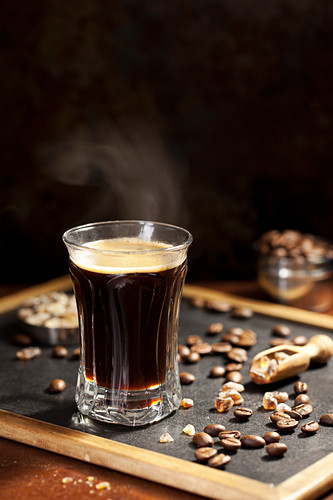 Steaming black coffee with coffee beans