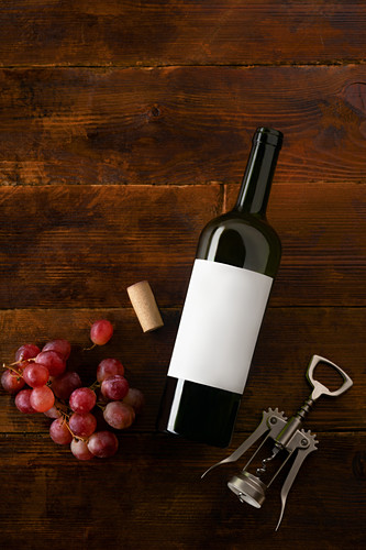 A wine bottle with a blank label, a corkscrew, corks and grapes