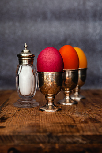 Easter eggs coloured with organic dyes in egg cups with a salt shaker