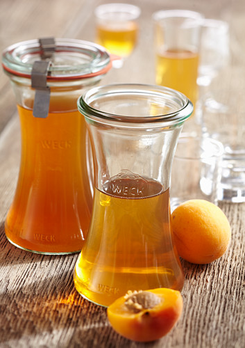 Homemade apricot liqueur with fresh fruit, seeds and cognac