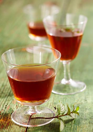 Homemade peppermint liqueur with wine spirit, mint, nutmeg, cloves, orange and sugar