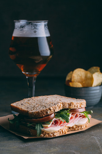 Delicious sandwich with ham, cheese, lettuce and tomato with a glass of beer and chips