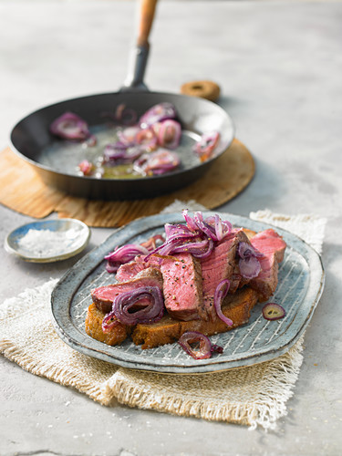Opened steak sandwich with fried onions from a pan