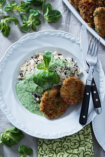 Mixed rice with millet and vegetable patties and lambs lettuce cream sauce (vegan)
