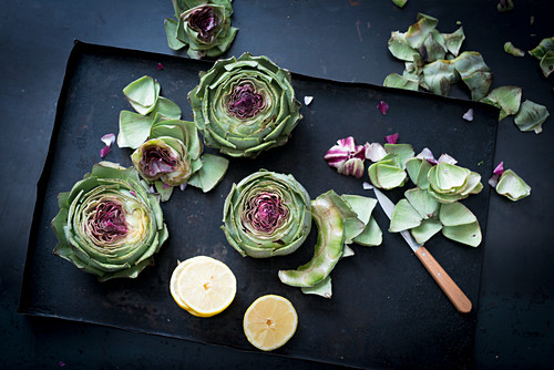 Fresh artichokes with lemons on a baking sheet