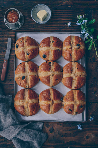 Hot-cross buns with dried cherries on a baking tray