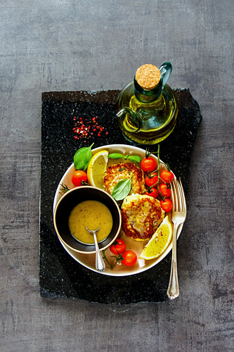 Flat lay of homemade vegetarian cauliflower cakes with sauce and fresh vegetables
