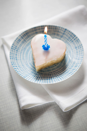 Miniature heart shaped cake with a burning candle