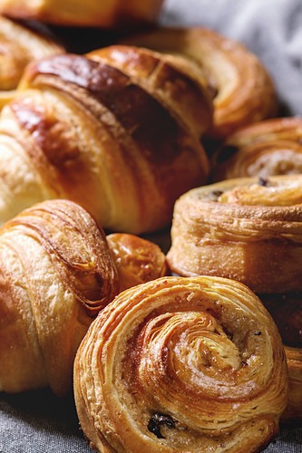 Variety of homemade puff pastry buns, cinnamon rolls and croissant