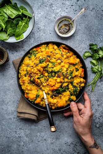 Vegan red lentil, chickpea and squash dahl with spinach in a bowl (India)