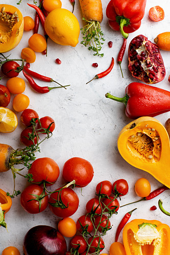 Flatlay with colorful vegetables arranged on white background (Tomatoes, squash and peppers)