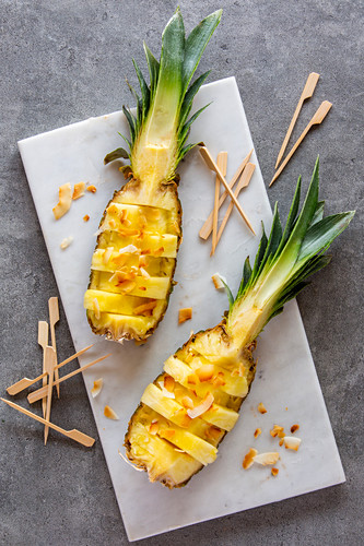 Pineapple boats with roasted coconut chips and wooden skewers on a white marble platter