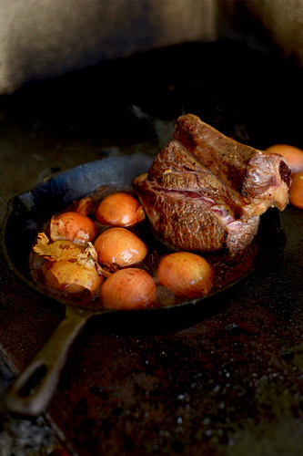 Beef with onions in a cast-iron pan