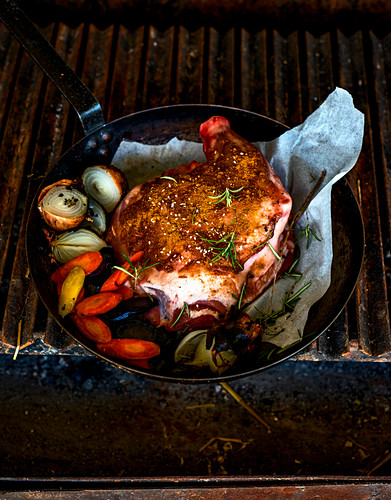 Spiced lamb shoulder in an iron pan on a grill