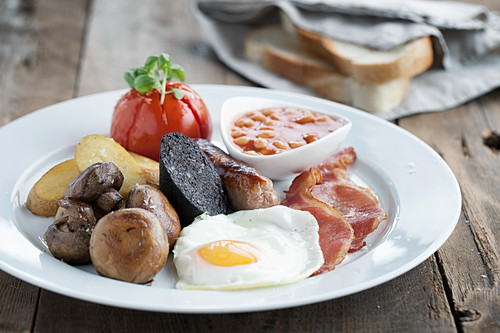 English Breakfast served on a white plate with white sliced bread in the background